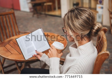 Woman reading a paper book with a cup of coffee in outdoor cafe, hobby