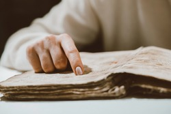 Woman reading ancient book - Bible. Concentrated attentively follows finger on paper page in library. Old archival manuscripts. History concept. High quality