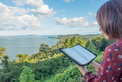 Woman reading bible on Mountain with sky and sea background