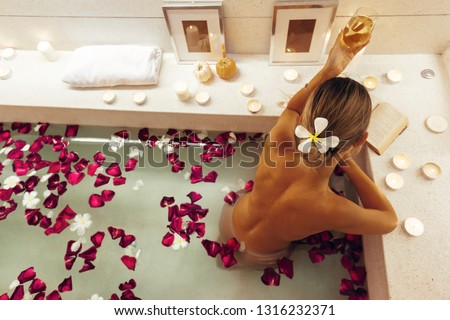 Woman reading book and drinking wine while relaxing in luxury spa bath decorated with candles, top view from above. Spending romantic evening or night in bathroom.
