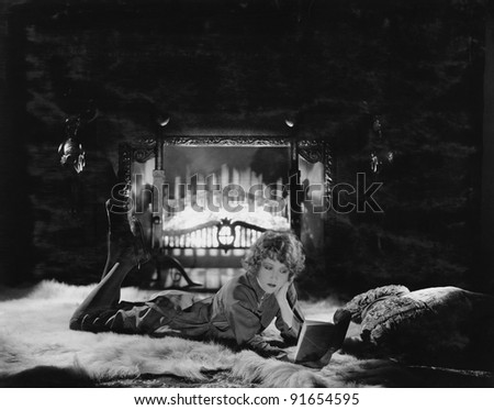 Woman reading book by the fire