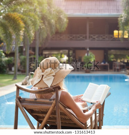 woman reading book in deck chair near swimming pool