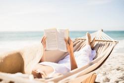 Woman reading book in hammock on the beach