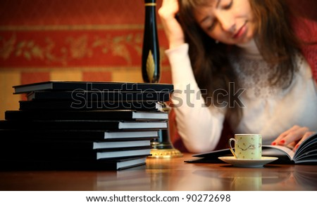 Woman reading book in office desk cup of coffee on (focus on books and cup)