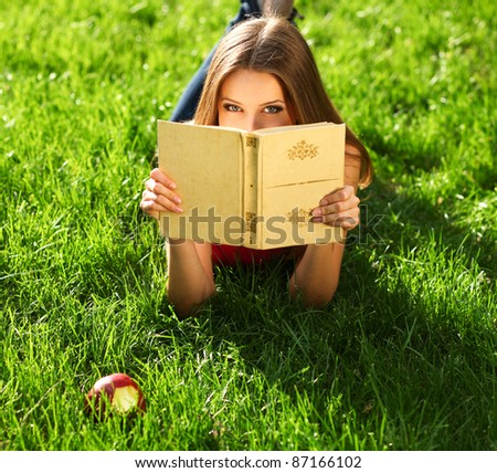 Woman reading book in the park on the grass