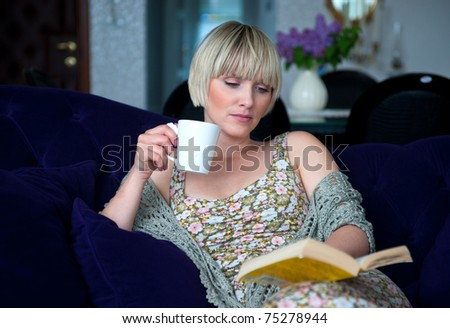 woman reading book nd drinking coffee while sitting on the sofa at home living room