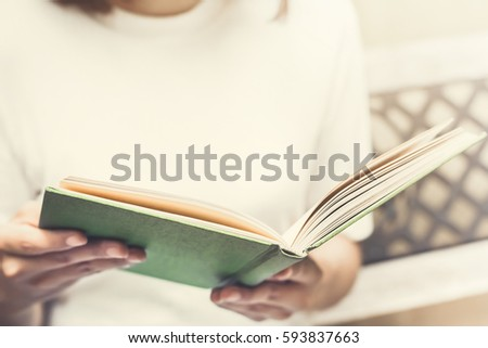 woman reading book on the bench ...