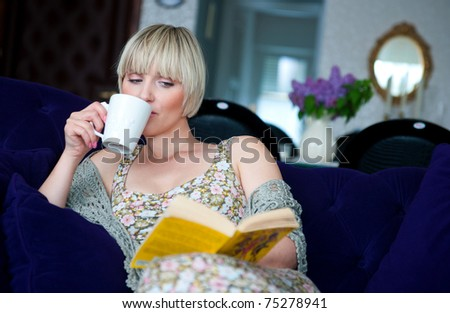 woman reading book sitting on the sofa at home living room