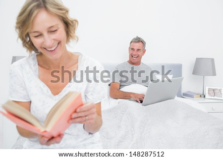 Woman reading book while husband is using laptop in bedroom at home