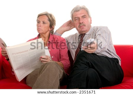 Woman reading book while man watching television