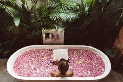 Woman reading book while relaxing in bath tub with flower petals. Organic spa relaxation in luxury Bali outdoor bath.