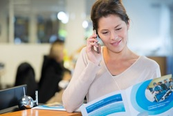 woman reading brochure and making telephone enquiry
