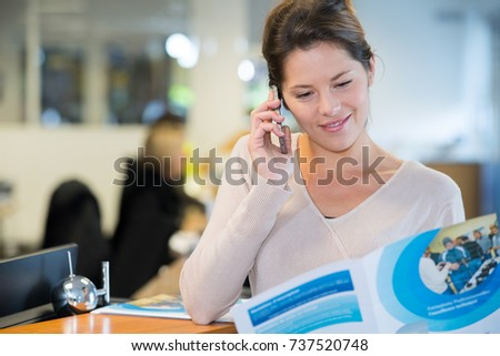 woman reading brochure and making telephone enquiry #737520748