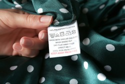 Woman reading clothing label with care instructions and content information on green polka dot garment, closeup
