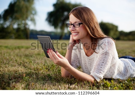 Woman reading e-book in nature.