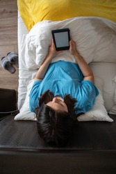 woman reading electronic book in bed.