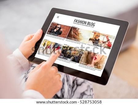 Woman reading fashion blog on tablet