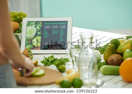 Woman reading green smoothie formula on tablet when cooking
