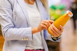Woman reading ingredients and nutrition information on juice bottle's etiquette