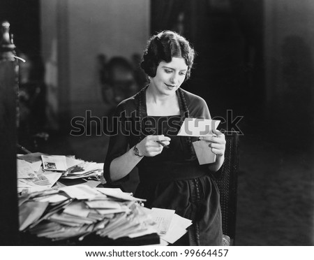 woman reading letter with pile...