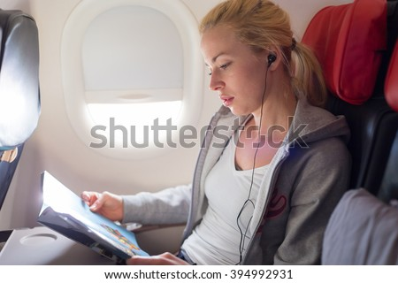 Woman reading magazine and listening to music on airplane. Female traveler reading seated in passanger cabin. Sun shining trough airplane window.