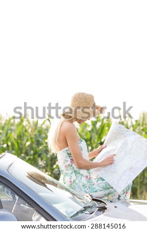 Woman reading map while leaning on convertible against clear sky