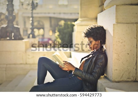 Woman reading outdoors #594429773