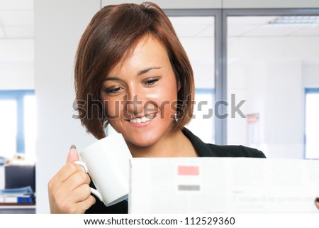 Woman reading the newspaper while drinking coffee