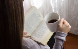 woman reading with a cup of coffee