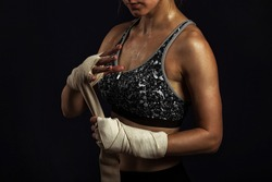Woman ready for fight concept. Boxer fighter girl in sports top, wraps his hands elastic bandages fists on black