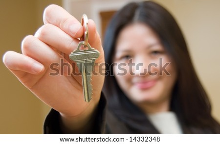 Woman Realtor offering key to house - stock photo