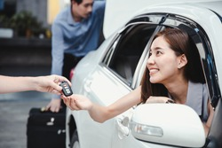 Woman received the keys from the car rental shop after entering into the contract. Young smiling woman getting key of a new car. Concept for car rental.