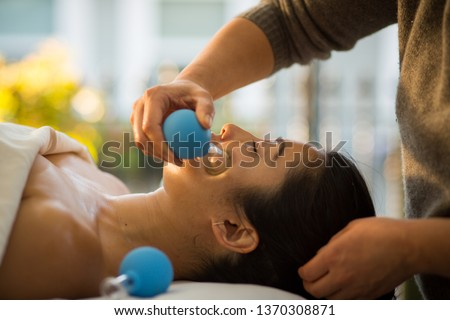 Woman receives facial cupping massage facial rejuvenation at acupuncture wellness spa