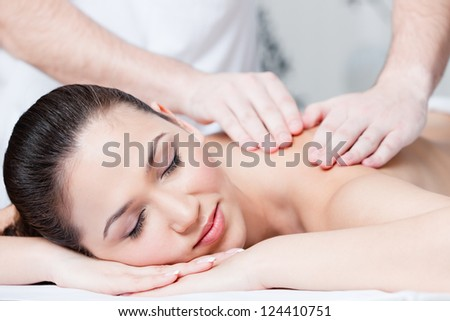 Woman receives relaxing body massage at spa salon
