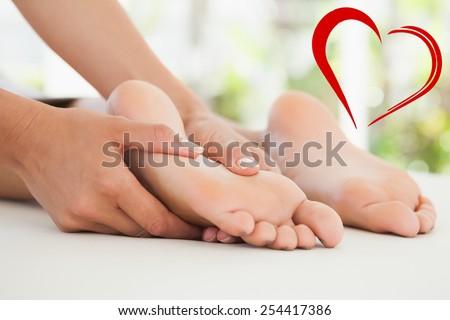 Woman receiving a foot massage against heart