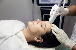 Woman receiving HUFU therapy- high intensity focused ultrasound treatment on face. Therapist doing non-surgical cosmetic plasma lift on client forehead with ultrasonic device. SMAS lifting
