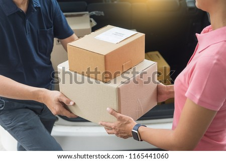 Woman receiving parcel cardboard box from delivery man Carrying Courier Shipping Mail from making an online order while standing in front of the house Stock photo ©