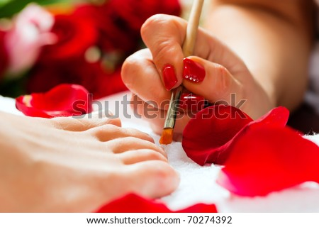 Woman receiving pedicure in a Day Spa; lots of flowers in the background