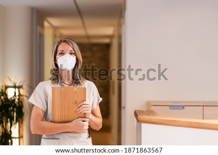 woman receptionist holding folder with documents and with mask in hospital Stock photo ©