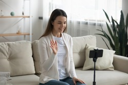 Woman record new videovlog sit on couch in living room. Puts smartphone on tripod girl wave hand greets subscribers make online live stream, lead webinar distant chat, modern tech, video event concept