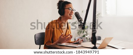 Woman recording a podcast on her laptop computer with headphones and a microscope. Female podcaster making audio podcast from her home studio.