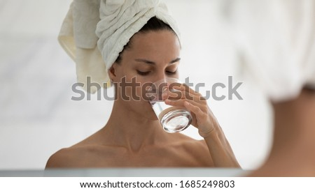 Woman reflected in mirror while drinking water. Reduce of thirst, water balance weight control, caring about beauty of skin, hangover relief, start new day, healthy habit, prevent of body dehydration