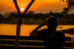 Woman reflecting in the sunset. Tia Nair Park in the city of Cuiabá - Mato Grosso.