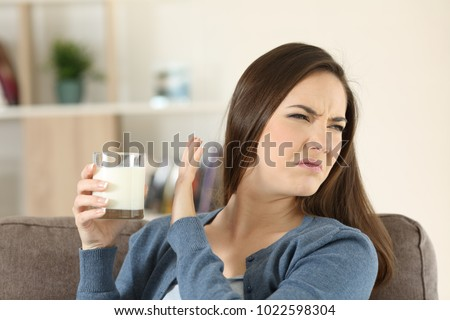 Woman refusing a glass of milk sitting on a couch in the living room at home
