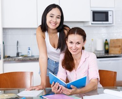 Woman rejoicing at good marks of her teenage daughter in kitchen