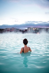 Woman relaxes and enjoys of spa in hot spring Blue Lagoon in Iceland