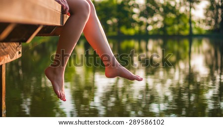 Woman relaxes by the lake sitting on the edge of a wooden jetty , swing one\'s feet near the water surface. Sunny joyful summer day or evening concept.