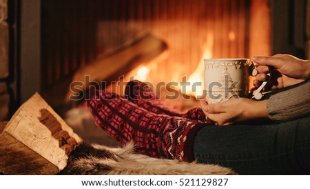 Woman relaxes by warm fire with a cup of hot drink and wriggles her toes in woollen socks. Close up on feet. Winter concept.  #521129827