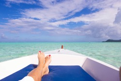 Woman relaxes on bow of boat over clear, turquoise water on tropical island Bora Bora in French Polynesia