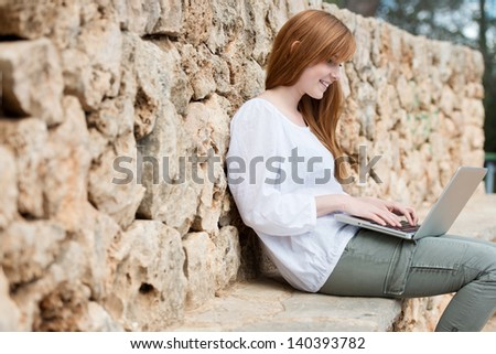 Woman relaxing against a stone wall on a ledge sitting typing on her laptop computer balanced on her lap
